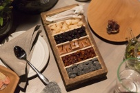 A_wooden_box_filled_with_tar_pastrilles__meadowsweet_candy__dried_rowansberries__smoked_caramel__sunflower_seed_nougat__dried_balck_currants.jpg