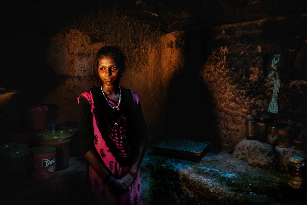 Radhu Krishnan - In seguito ad un incidente in moto alcuni anni fa, il padre si ruppe la spina dorsale e una gamba; ha ricominciato pochi mesi fa a camminare e cerca di trovare lavoretti poco faticosi da fare per non continuare ad essere un peso per la famiglia. La madre va a lavorare presso il Comune, in un progetto governativo che offre 100 giorni di lavoro garantito all'anno per le donne che appartengono a famiglie sotto la soglia di povertà. Fanno lavori utili alla comunità, come la ripulitura delle scuole, delle strade e dei giardini e la raccolta differenziata dei rifiuti. Il salario è di 186 rupie al giorno, cioè meno di tre euro. R. K. ha un fratello più grande che dorme con il papà sull'unico letto in casa, mentre lei e la mamma dormono per terra. Hanno la connessione alla rete elettrica, che alimenta 5 lampadine e un macina-spezie e utilizzano un fiume nelle vicinanze della loro casa nella foresta (dove si vedono passare anche elefanti) per lavare se stessi e i loro vestiti.