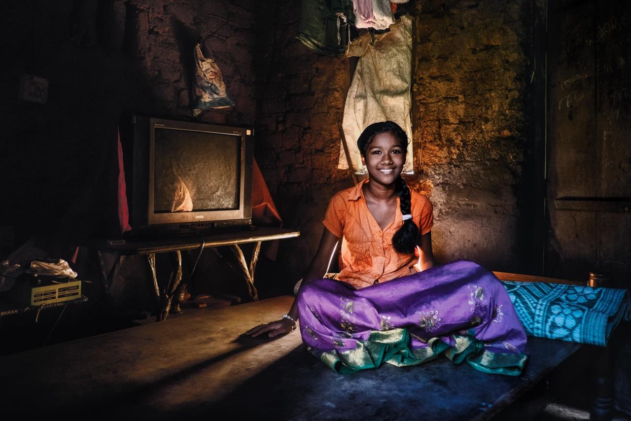 """Devika Taulasi - Raggiungere casa di questa ragazza non è stato semplice e l?impresa compiuta per arrivarci, una salita impressionante, è valsa uno splendido paesaggio, ma oltre questo qui non c'è molto altro! Lei e la sua famiglia vivono nella casa di sua zia situata nel villaggio Thekkada. Questa casa è costruita di mattoni di fango e il tetto è fatto con foglie di cocco. Ultimamente hanno ricevuto in dono un telo blu che copre il tetto durante i monsoni e durante l'attacco """"dispettoso"""" delle scimmie di notte. Il papà ha abbandonato la famiglia 11 anni fa e lei vive con la nonna e sua sorella oltre naturalmente a sua mamma che lavora in una fabbrica di anacardi (solo quando c'è richiesta)."""